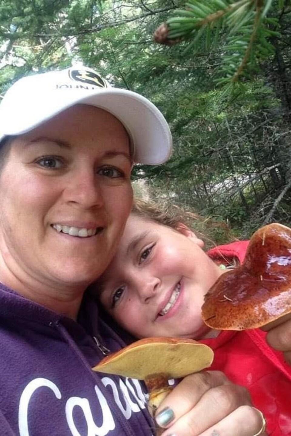 Une femme qui cueille un champignon avec sa fille.