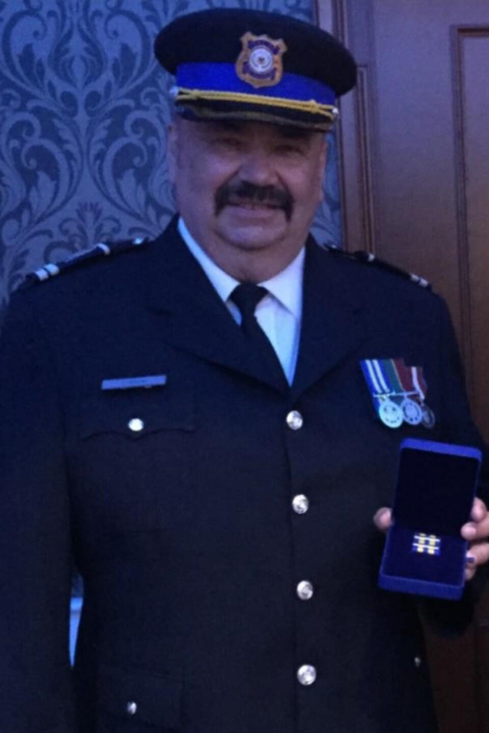 Floyd McBride pose en uniforme, une médaille dans un boîtier à la main.