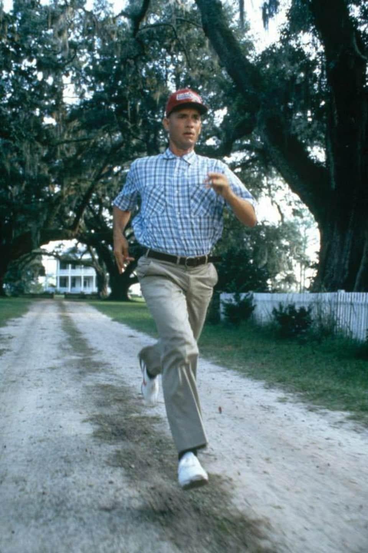 Un homme court sur une route de terre entourée d'arbres.
