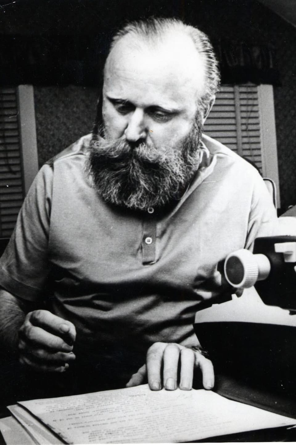 L'homme porte une grosse barbe et semble annoter une page manuscrite.