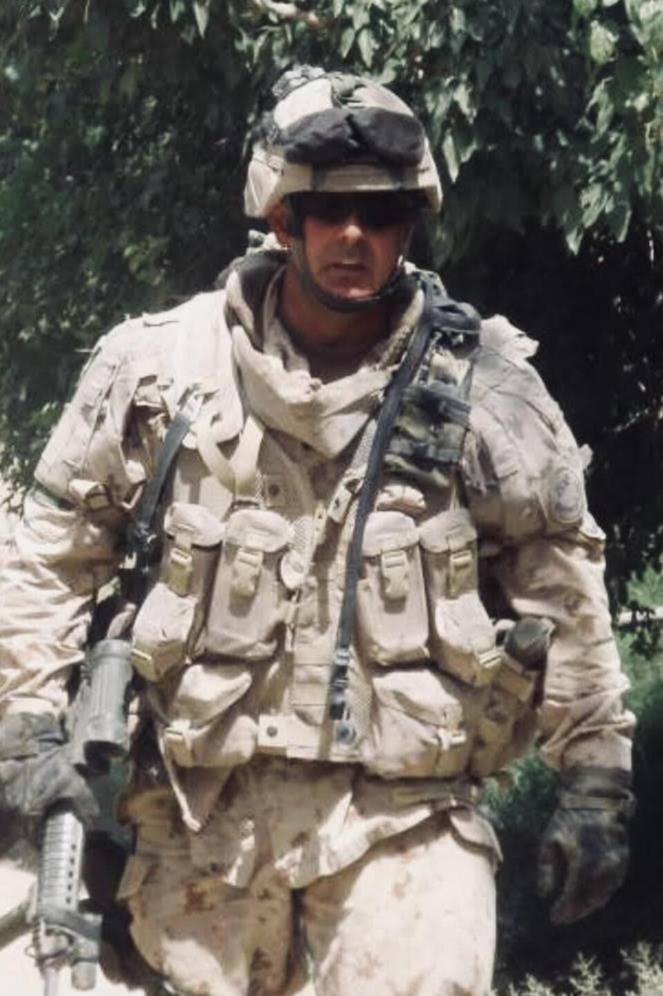 Gino Savard est en habit de camouflage et armé sur le terrain en Afghanistan.
