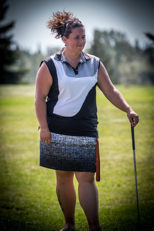 Une femme pose avec son fer de golf.