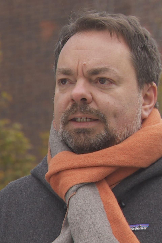 Yannick Beaudoin, photographié dehors, porte une écharpe orange et grise.