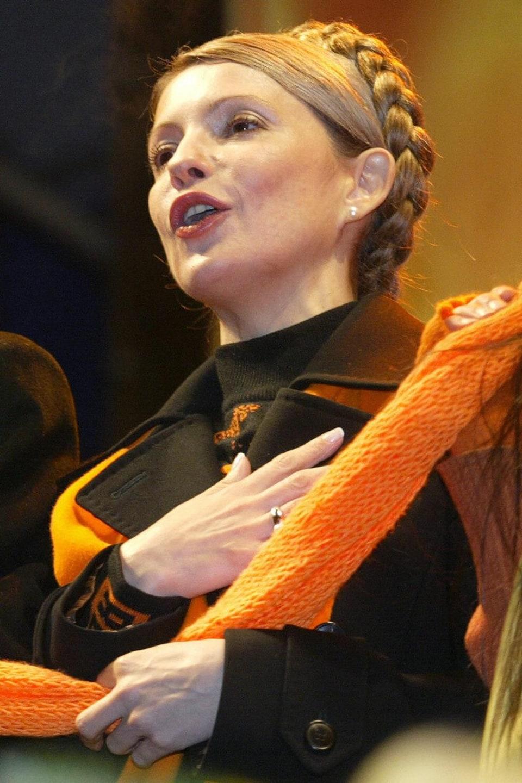 Ioulia Timochenko et Viktor Ianoukovitch chantent, main sur le coeur, enveloppés d'une écharpe orange.