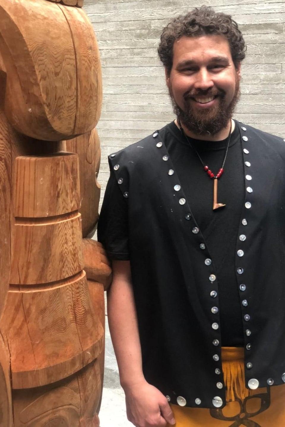 L'artiste pose en habit traditionnel à côté d'un totem de bois.