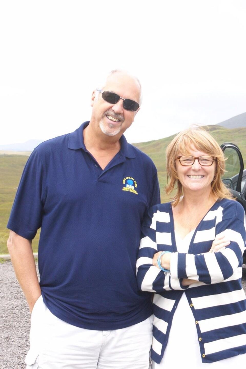 Un homme et une femme regardent le photographe et sourient dans un paysage écossais.