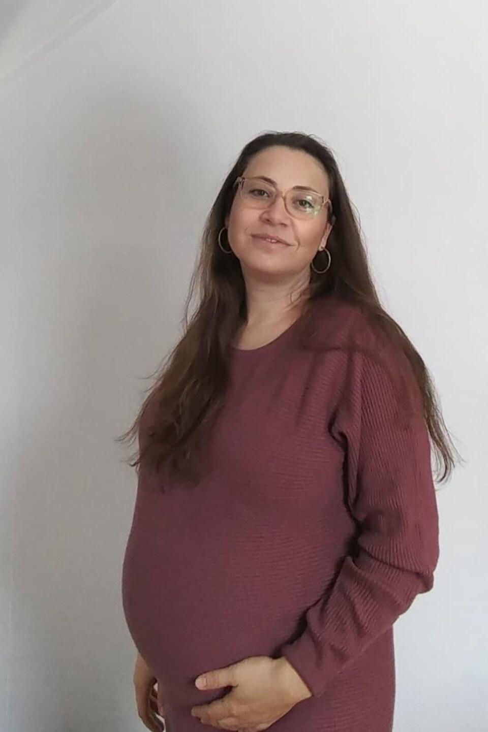Une femme enceinte sourit à la caméra, soutenant son ventre.