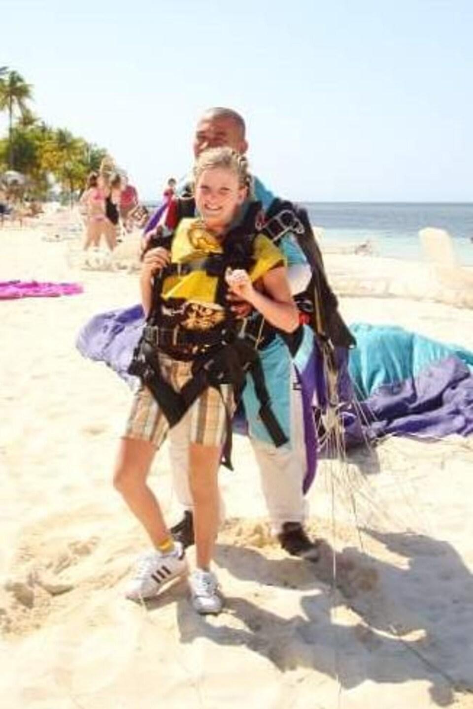 Karine Duval prête à sauter en parachute, sur une plage face à l'océan