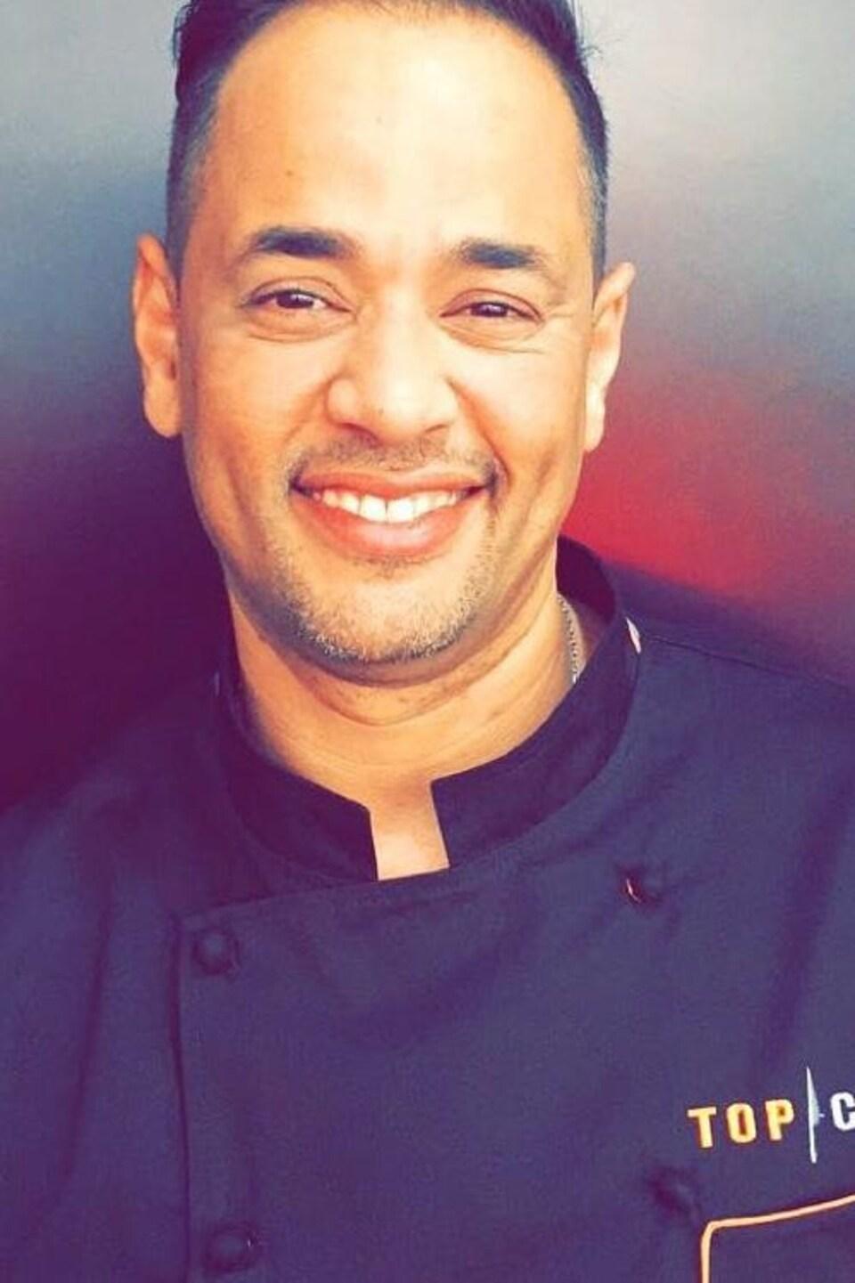 Gros plan de Khalid Kahya, vêtu de son uniforme de chef avec le logo Top Chef.