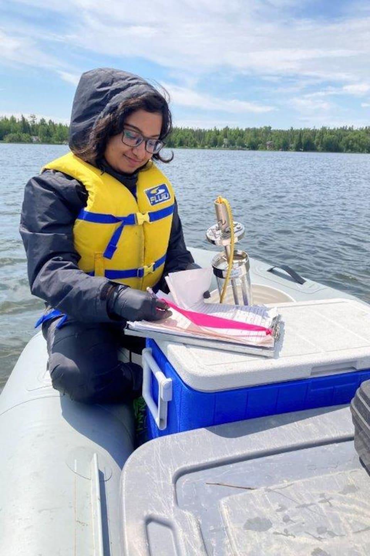 Tasnim Anjum Mou prend des notes tandis qu'elle se trouve sur un bateau.