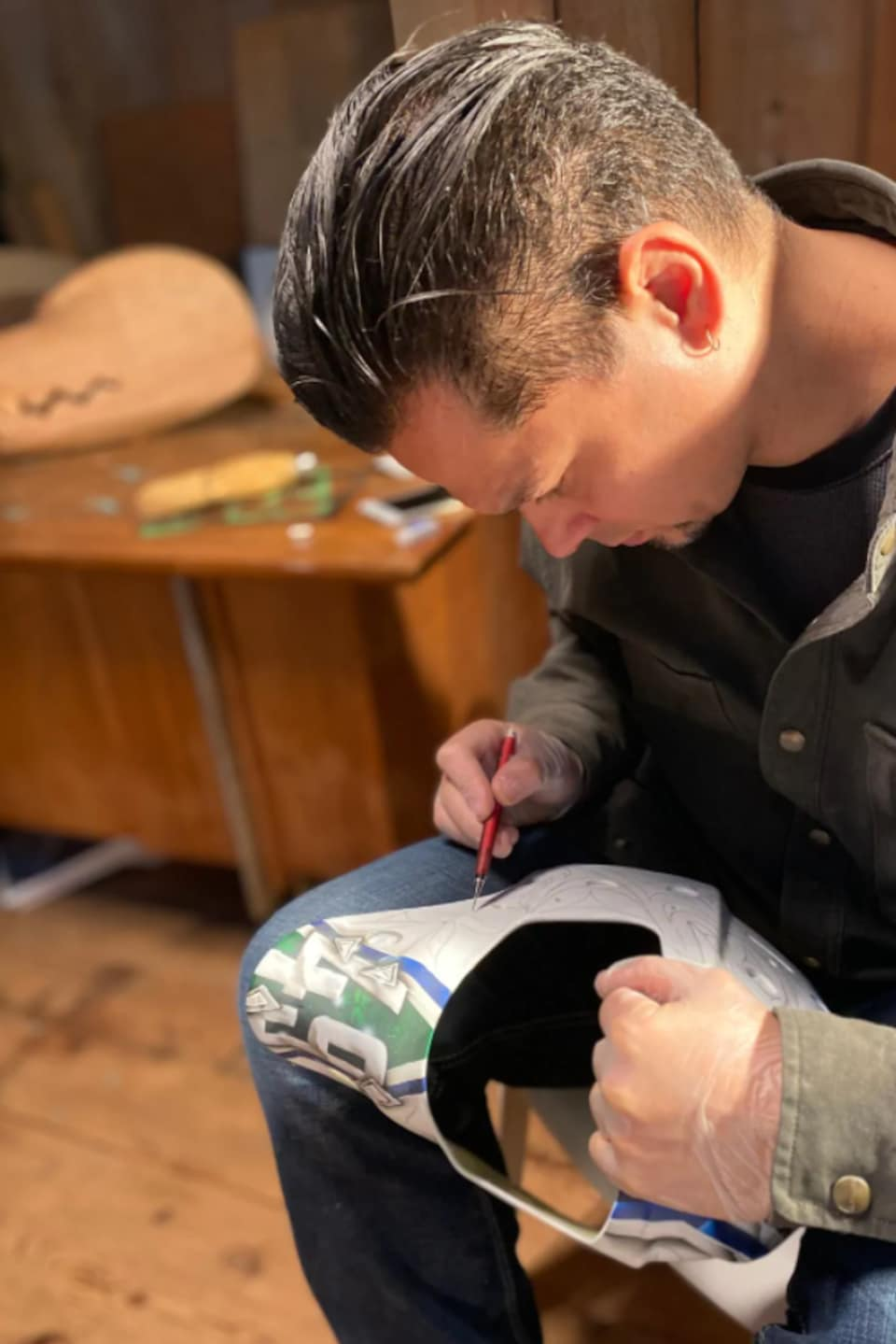 Luke Marston peint à la main le masque dans son atelier.