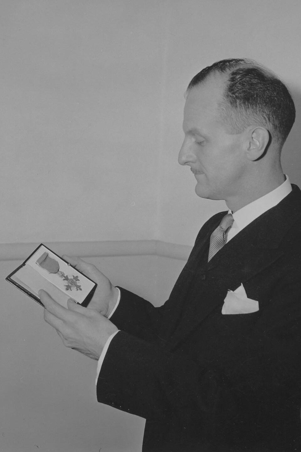 Marcel Ouimet pose en regardant son insigne de l'Ordre de l'Empire britannique placé dans un coffret.