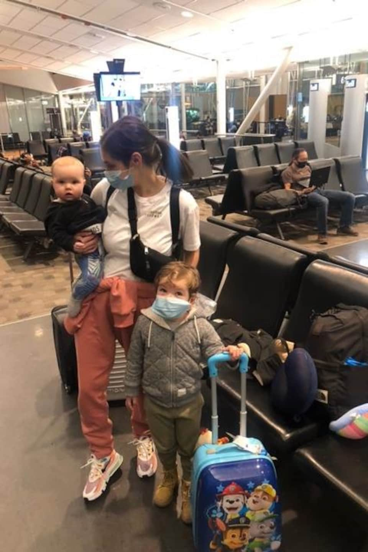 Une mère avec ses deux enfants à l'aéroport.