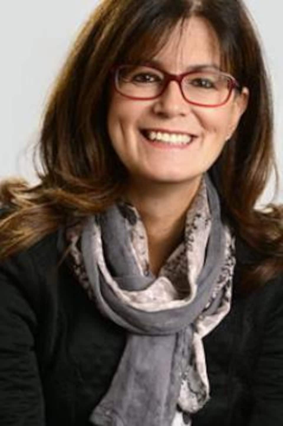 Femme souriante et portant des lunettes, photographiée en gros plan.