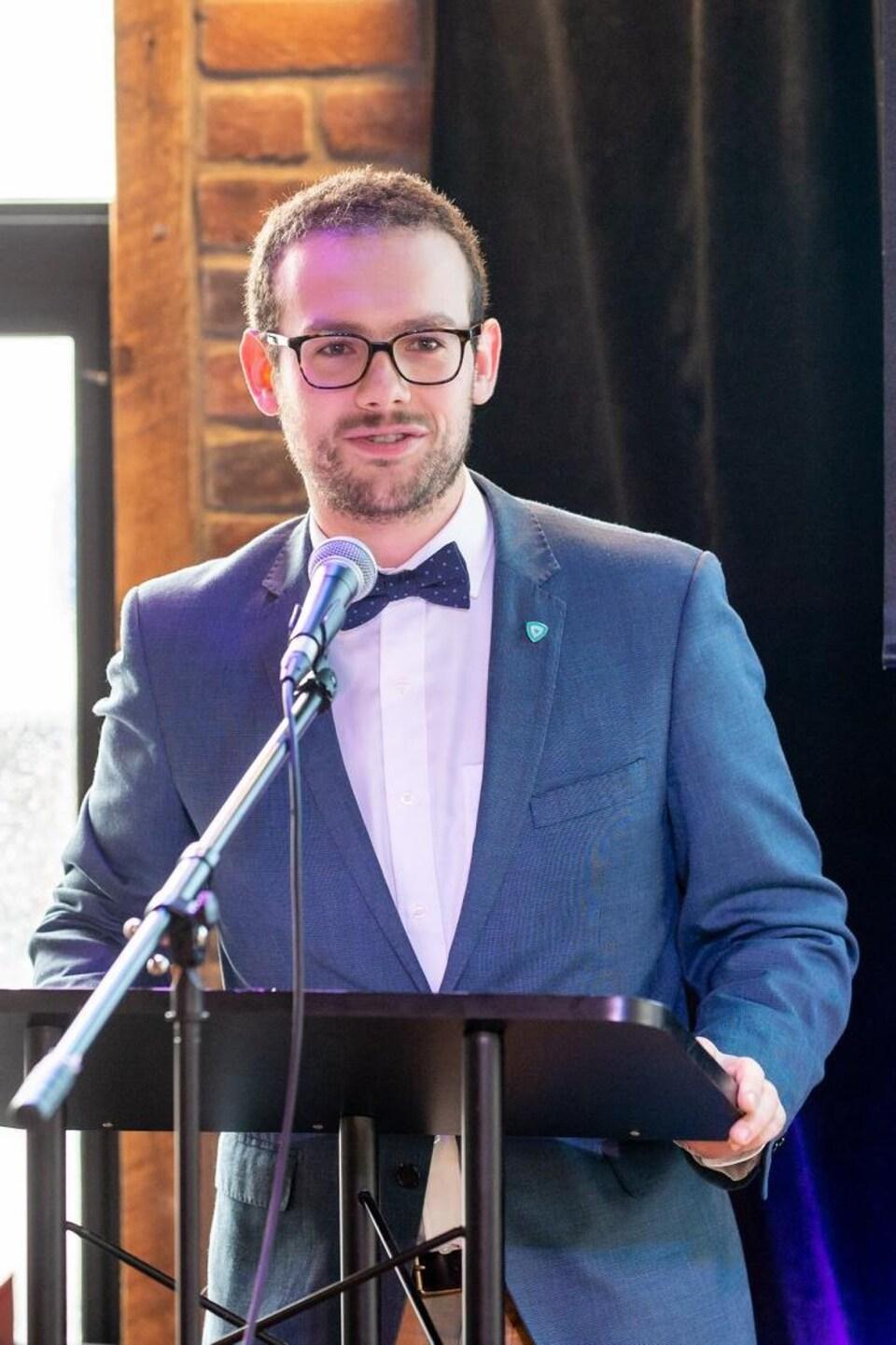 Un homme qui porte un noeud papillon prononce un discours.