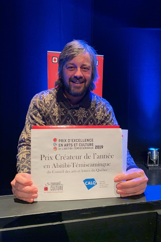 Un homme tient un certificat indiquant «Prix Créateur de l'année en Abitibi-Témiscamingue du Conseil des arts et des lettres du Québec».