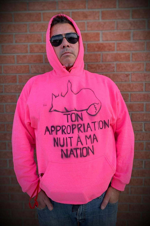Jacques T. Watso porte un chandail sur lequel il est écrit : Ton appropriation nuit à ma nation.