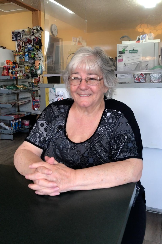 Monique Baril donne une entrevue assise à une table du restaurant, les mains croisées devant elle.