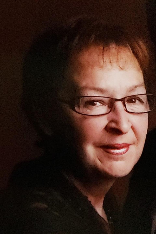 Visage d'une femme aux cheveux bruns et portant des lunettes.