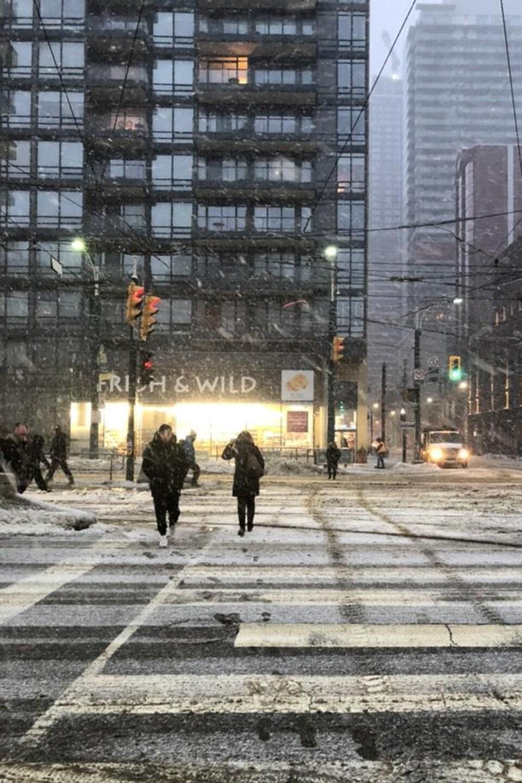 Photo de piétons qui traversent la rue sous la neige devant une tour d'habitation.