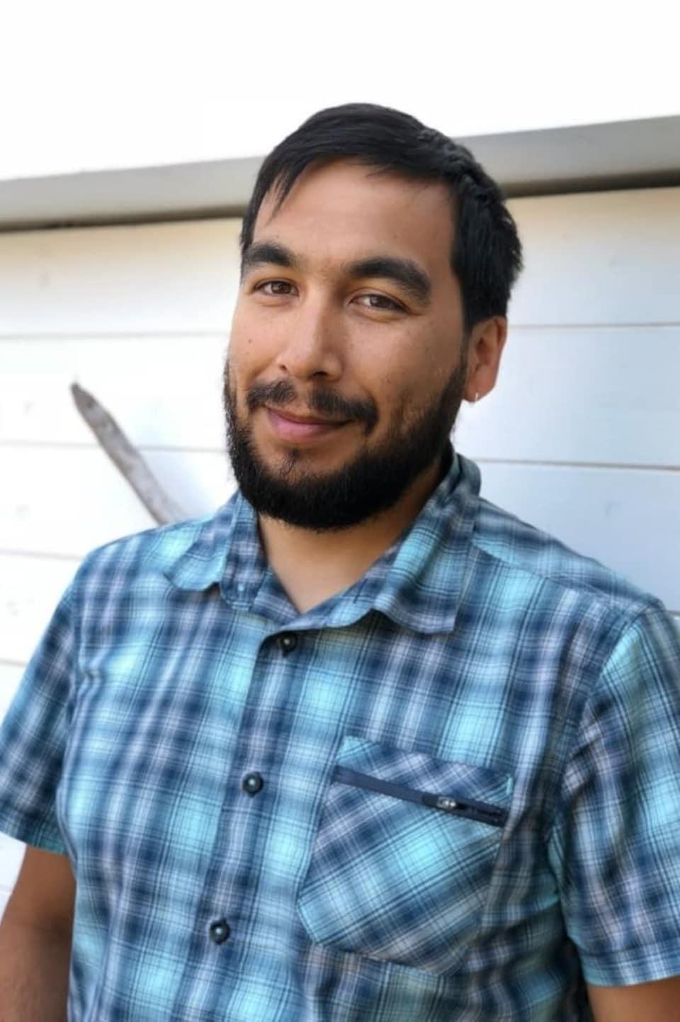 Un homme barbu pose à l'extérieur.