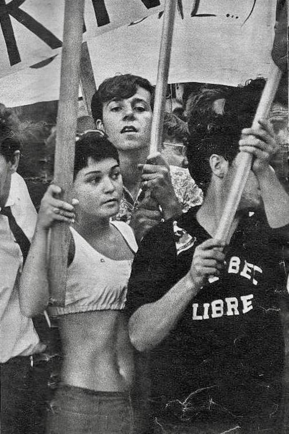 Jocelyne Robert au milieu d'une foule brandit une pancarte.