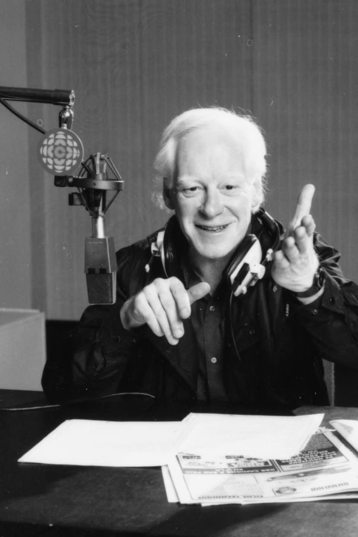 L'animateur Pierre Bourgault, des écouteurs encerclant son cou, est assis à une table où reposent ses notes qu'il tient d'une main. Près de sa tête, on voit un micro suspendu qui porte une affichette avec le logo de Radio-Canada.