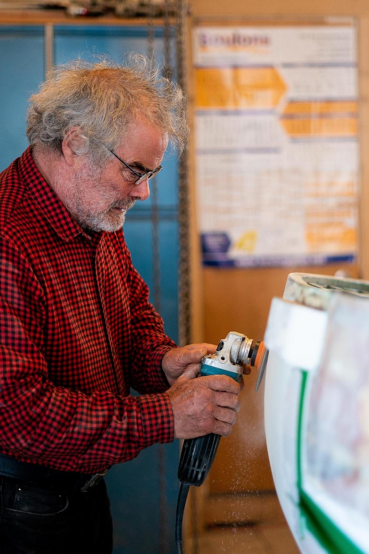 Daniel St-Pierre avec un outil électrique à la main en train de restaurer la surface d'une vieille chaloupe.
