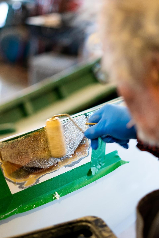 Daniel St-Pierre applique une fibre de verre sur la chaloupe qu'il restaure.