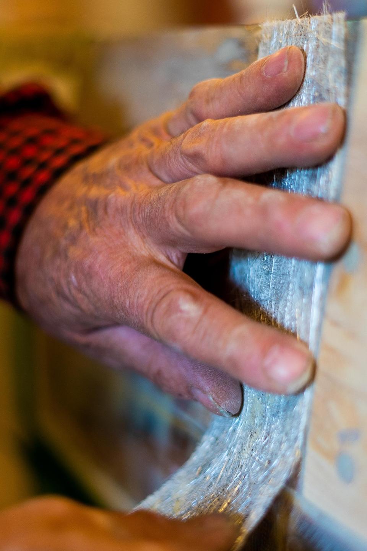 Plan sur la main de Daniel St-Pierre qui applique la fibre de verre sur la chaloupe.