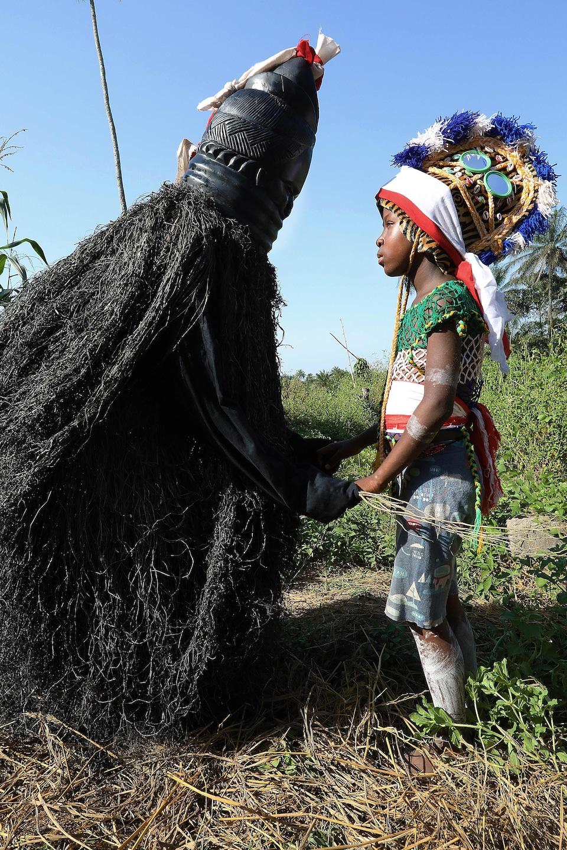 Une jeune fille tient les mains d'une personne déguisée