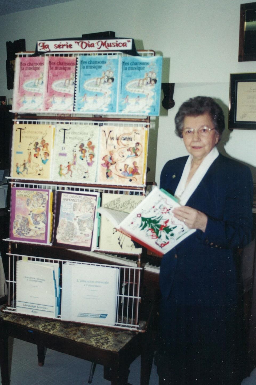 Soeur Thérèse Potvin pose à côté d'un présentoir où sont exposés des livres d'apprentissage de la musique de la série « Via Musica ».