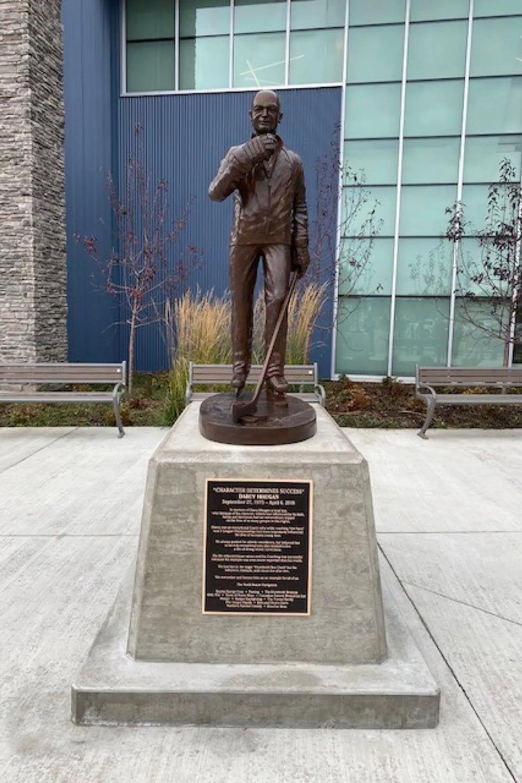 Une statue en bronze d'un homme avec un bâton de hockey.