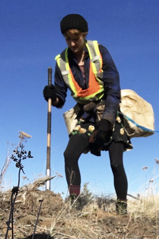Suzie Gagnon en train de creuser un trou avec une pelle pour planter un arbre.