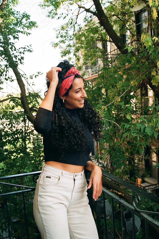 Une jeune femme tout sourire, habillée d'un jeans blanc et d'un chandail à manches longues noires, regarde est debout sur le balcon extérieur d'un appartement. Derrière elle, les branches et les feuilles d'un immense arbre.