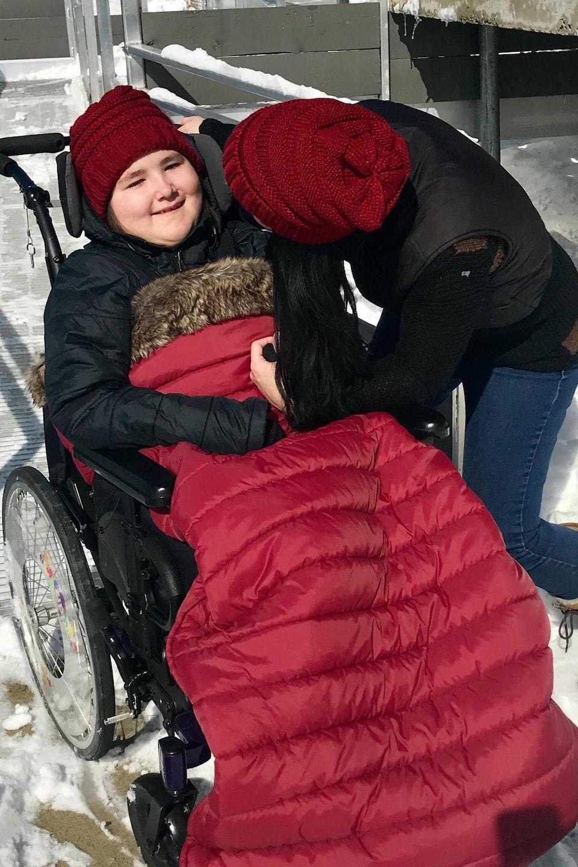 Une enfant en fauteuil roulant se fait donner une accolade par sa mère.