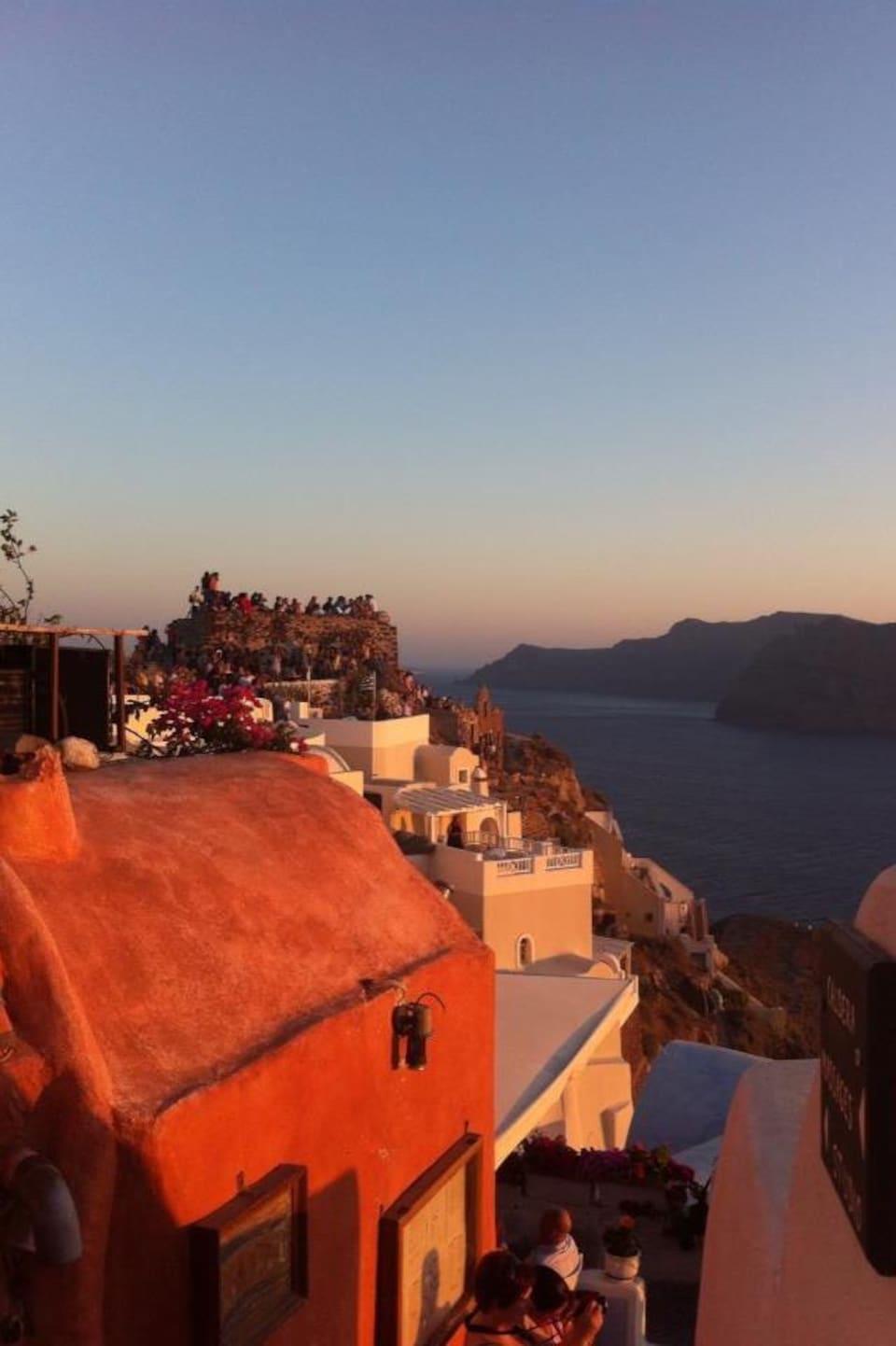 Des voyageurs admirent le coucher de soleil à Santorin.