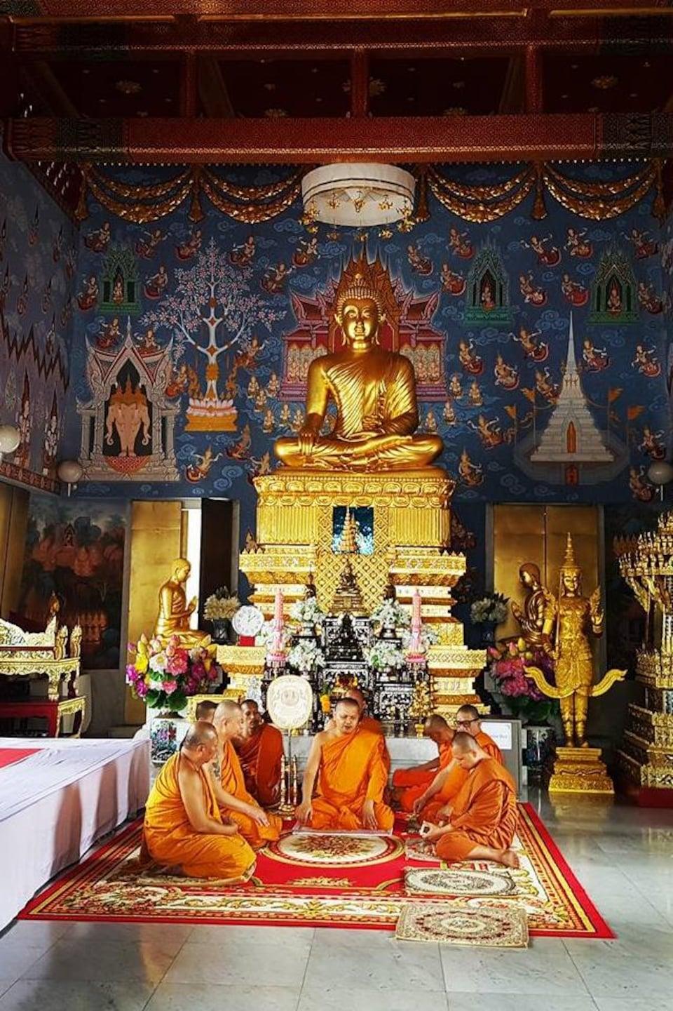 Des bouddhistes prient dans un temple de Bangkok, en Thaïlande.