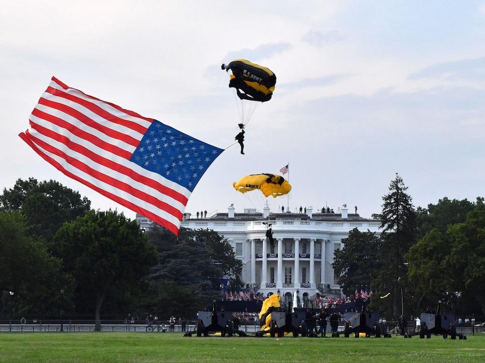 Deux parachutes et un grand drapeau volent au-dessus du parterre désert de la Maison-Blanche.