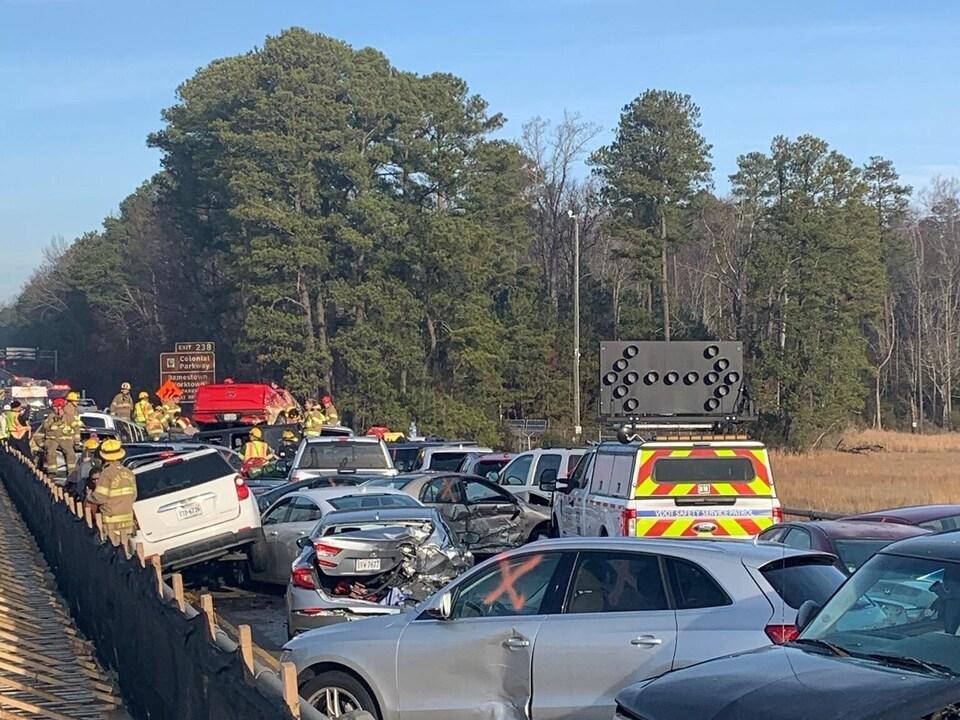 Des dizaines de véhicules sont prises dans un carambolage sur une route. Des pompiers s'affairent.