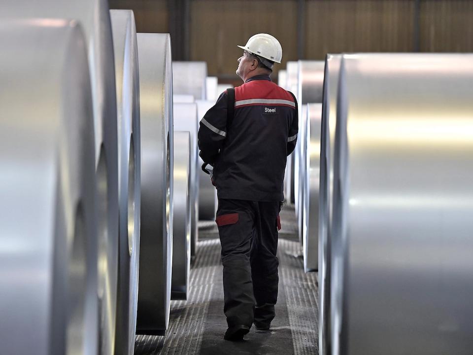 Un travailleur marche entre des rangées de bobines d'acier.