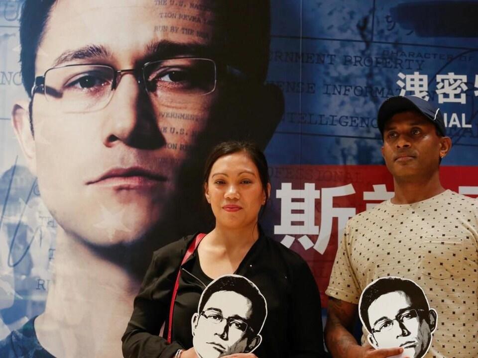 Les sans-papiers Vanessa Rodel et Ajith Pushpakumara posent devant une affiche du film «Snowden», en 2016, à Hong Kong.