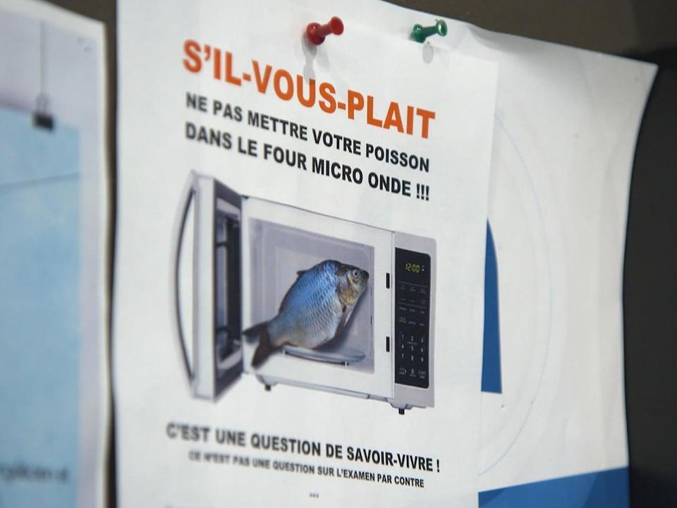 On voit une affiche où il est écrit «S'il-vous-plait, ne pas mettre votre poisson dans le four micro onde!!!»