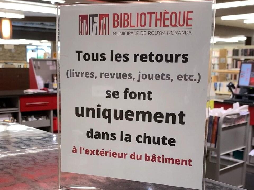 Une affiche indique «Tous les retours livres, revues, jouets se font uniquement dans la chute à l'extérieur du bâtiment».