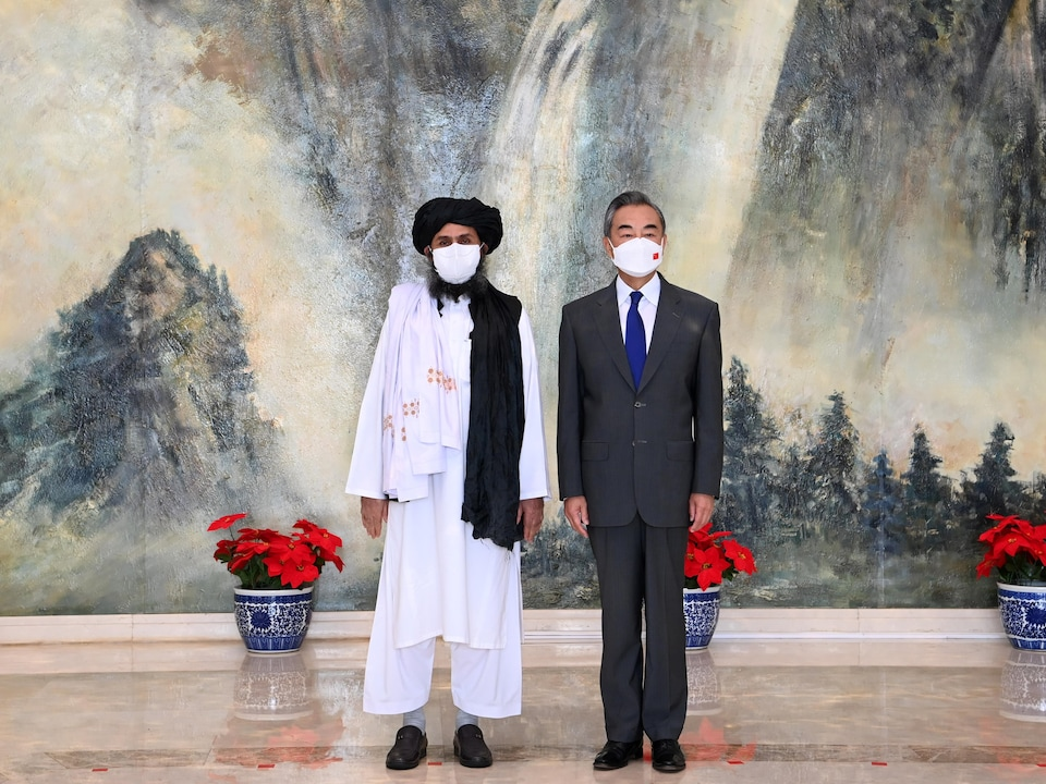 MM. Baradar et Wang portent des masques.