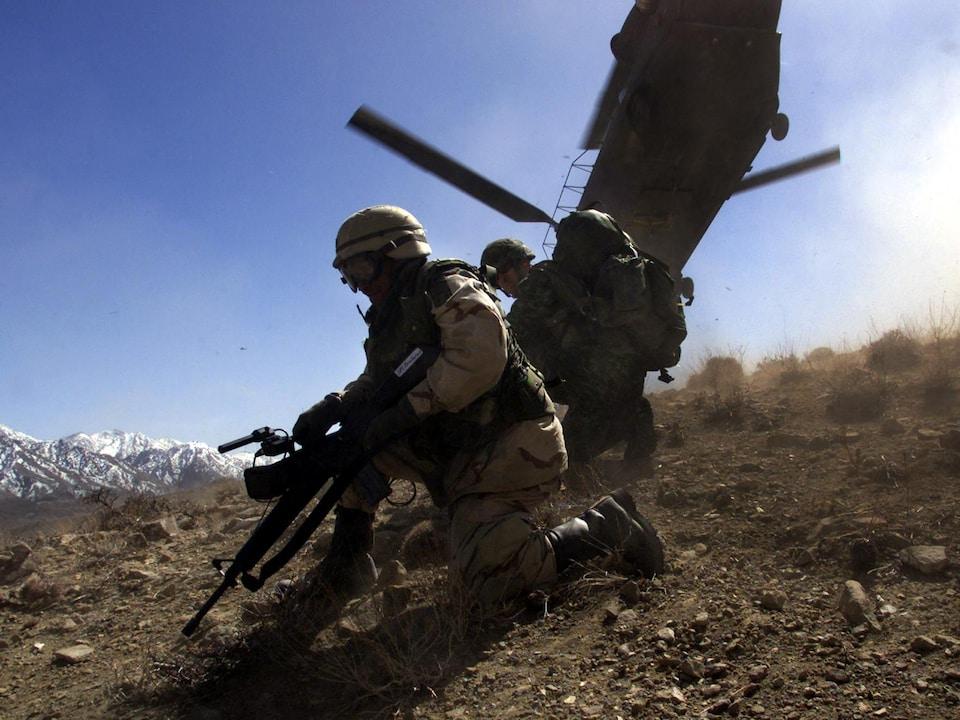 Des soldats sont accroupis devant un hélicoptère.