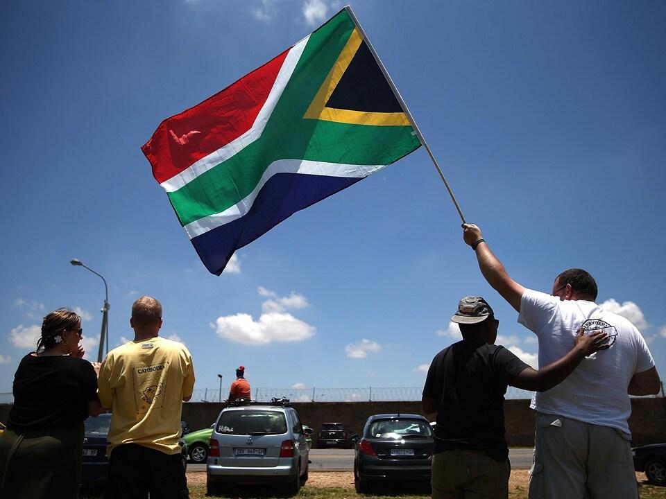 Le drapeau flotte dans un ciel bleu.