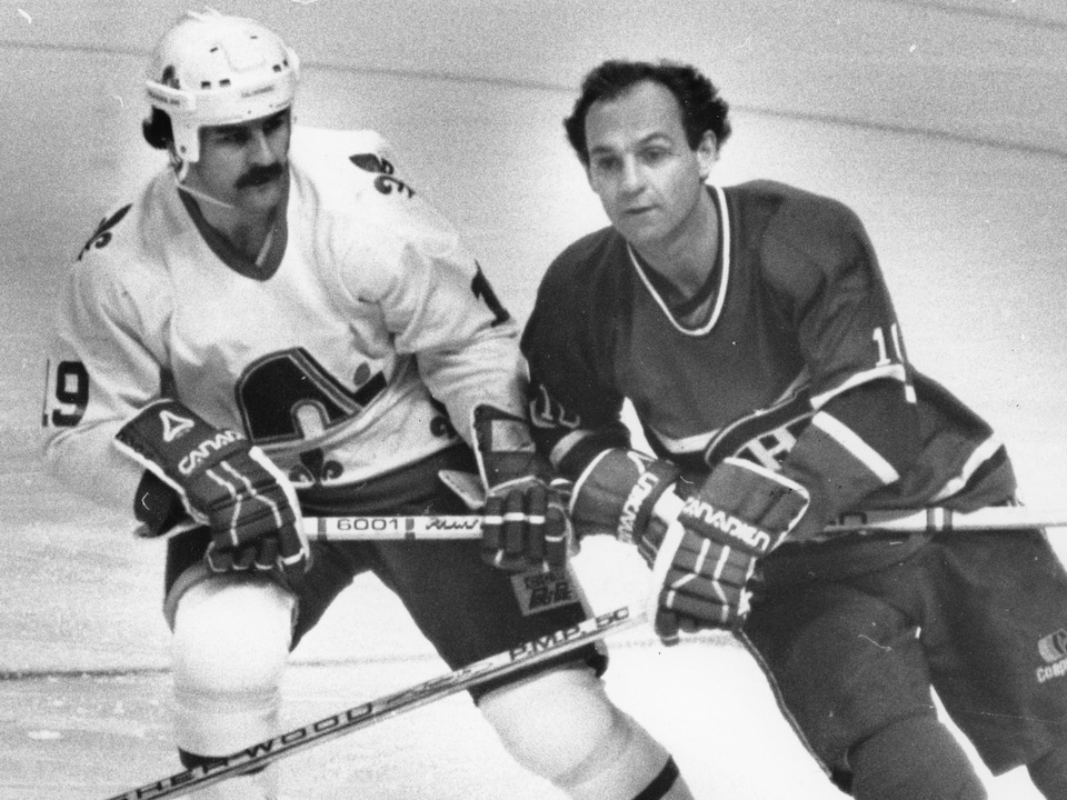 Alain Côté et Guy Lafleur lors d'un affrontement Canadien-Nordiques au Colisée en 1984. Côté tente d'entraver Lafleur avec son bâton, et Lafleur file cheveux aux vents le regard fixé droit devant lui.