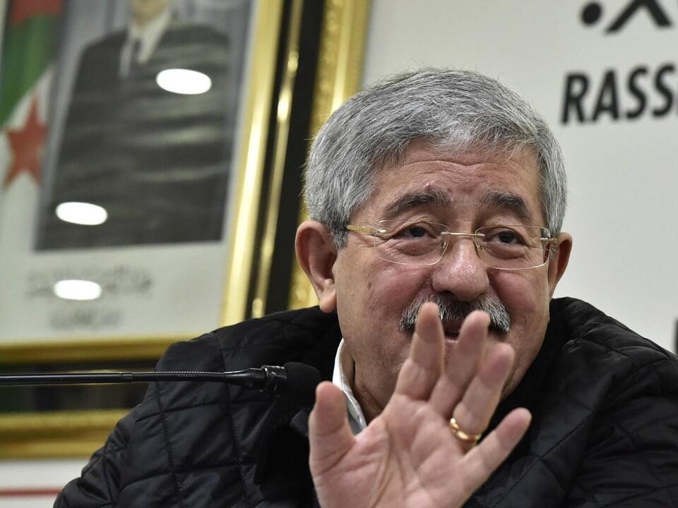 Un homme portant des lunettes fait un signe de la main alors qu'il parle derrière un micro.