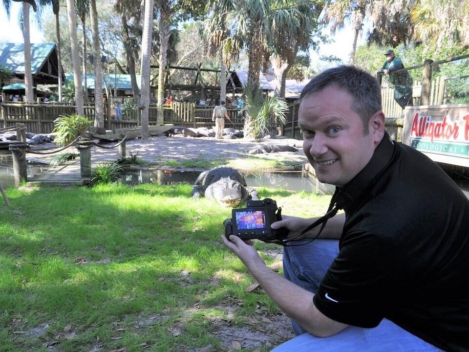 Un homme prend des images thermiques d'un alligator.